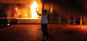 An armed man stands near the burning U.S. special mission in Benghazi Sept. 11, 2012